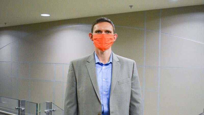 Parks poses with orange mask in suit at the top of a stairwell